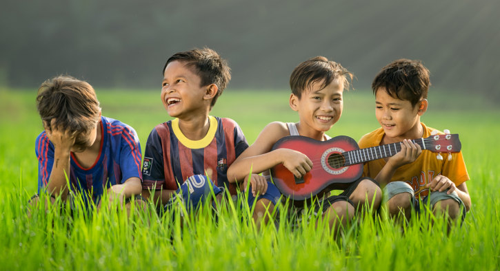 Four young boys sitting and having fun in a green meadow